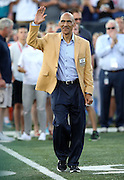 Former Tampa Bay Buccaneers and Indianapolis Colts head coach Tony Dungy waves while being announced over the public address system as he walks onto the field as a new member of the Pro Football Hall of Fame before the Green Bay Packers 2016 NFL Pro Football Hall of Fame preseason football game against the Indianapolis Colts on Sunday, Aug. 7, 2016 in Canton, Ohio. The game was canceled for player safety reasons due to the condition of the paint on the turf field. (©Paul Anthony Spinelli)
