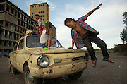 Children play on a beaten Lada car in front of an abandoned factory in Kyzyl, capital of Tuva Republic, southern Siberia, Russia. The factory used to process grain during Soviet times. Cut off from air and train traffic, this is one of Russia's poor regions.