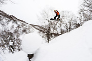 Alex Yoder pokes it backside through the trees and over a snow mushroom in the Niseko backcountry. Hokkaido, Japan.