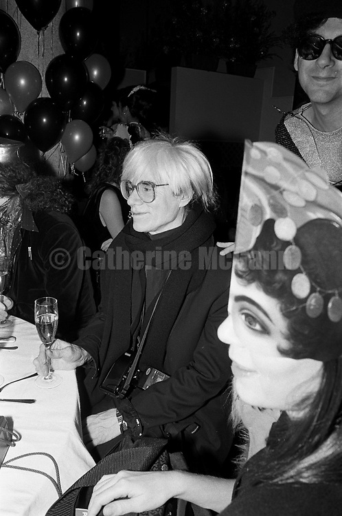 December 31, 1986:   Andy Warhol holds a glass of champagne and smiles as he celebrates his last New Year's Eve with a dinner at Cafe Roma restaurant in New York City, New York.  Village Voice writer Michael Musto on right with sunglasses. Warhol died less than two months later on February 22, 1987..