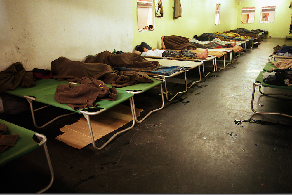 Immigrants sleep in prefabricated structures at a Red Cross emergency center near Calais. Many illegal immigrants stay at the center while the attempt to find passage across the English Channel to Britain..Sangatte, France. 21/06/2000.Photo © J.B. Russell