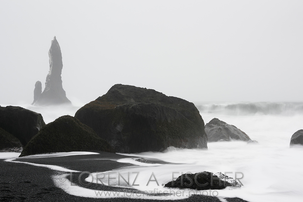 The volcanic rock formation Reynisdrangar rises from the northern Atlantic on a cloudy afternoon with heavy snowfall and a big surf in wintertime, village Vik, Icleand