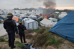 "Calais, Pas-de-Calais, France - 26.10.2016    <br />  <br /> Since the beginning of the governmental<br />  camp destruction on the day before many fires were placed by camp residents inside camp. Wide parts of the camp burned down. 3rd day of the eviction on the so called îJungle"" refugee camp on the outskirts of the French city of Calais. Many thousands of migrants and refugees are waiting in some cases for years in the port city in the hope of being able to cross the English Channel to Britain. French authorities announced a week ago that they will evict the camp where currently up to up to 10,000 people live.<br /> <br /> Seit dem Beginn der behoerdlichen Campzerstˆrung wurden zahlreiche Feuer im Camp gelegt. Weite Teile des Camps brannten ab. Dritter Tag der Raeumung des so genannte îJungleî-Fluechtlingscamp in der franzˆsischen Hafenstadt Calais. Viele tausend Migranten und Fluechtlinge harren teilweise seit Jahren in der Hafenstadt aus in der Hoffnung den Aermelkanal nach Groflbritannien ueberqueren zu koennen. Die franzoesischen Behoerden kuendigten vor einigen Wochen an, dass sie das Camp, indem derzeit bis zu bis zu 10.000 Menschen leben raeumen werden. <br /> <br /> <br /> / 261016"