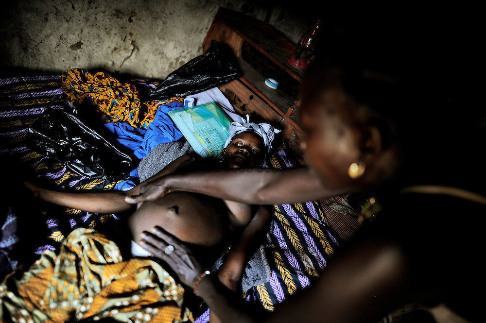 A traditional birth attendant examines the belly of Adamse Bangoa, 8 months pregnant with her first child. She will deliver her child on this bed and has never been to a doctor or the government hospital.