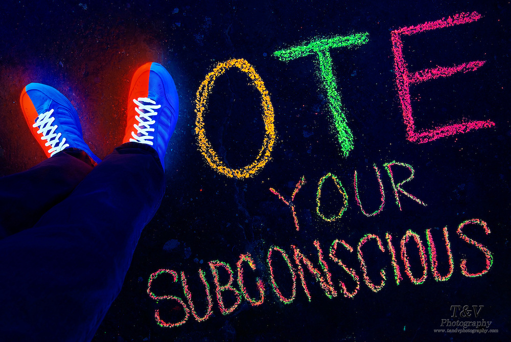 "Blacklight photography of glowing shows that form the shape of the letter V in a chalk drawing that spells ""Vote Your Subconscious""."