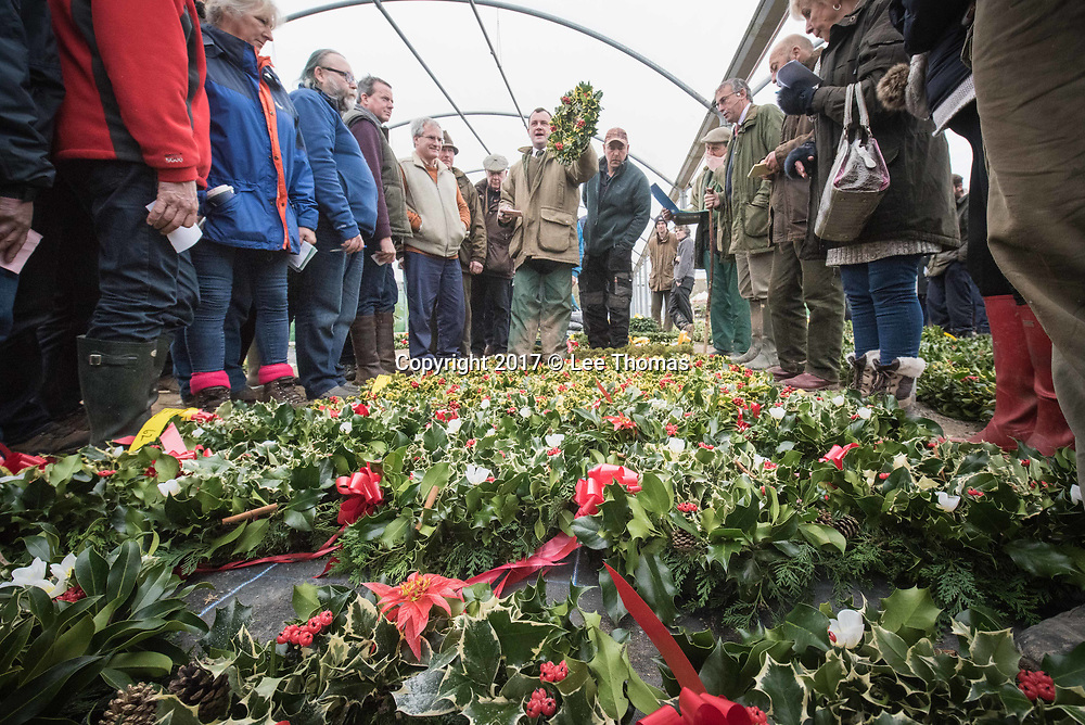 Burford House Garden Stores, Tenbury Wells, Worcestershire, UK. 5th December 2017. Buyers flock to Burford House in Tenbury Wells to take part in the annual mistletoe, wreaths, holly and Christmas tree auctions. Pictured: Buyers gather round the auctioneer selling holly wreaths. // Lee Thomas, Tel. 07784142973. Email: leepthomas@gmail.com  www.leept.co.uk (0000635435)