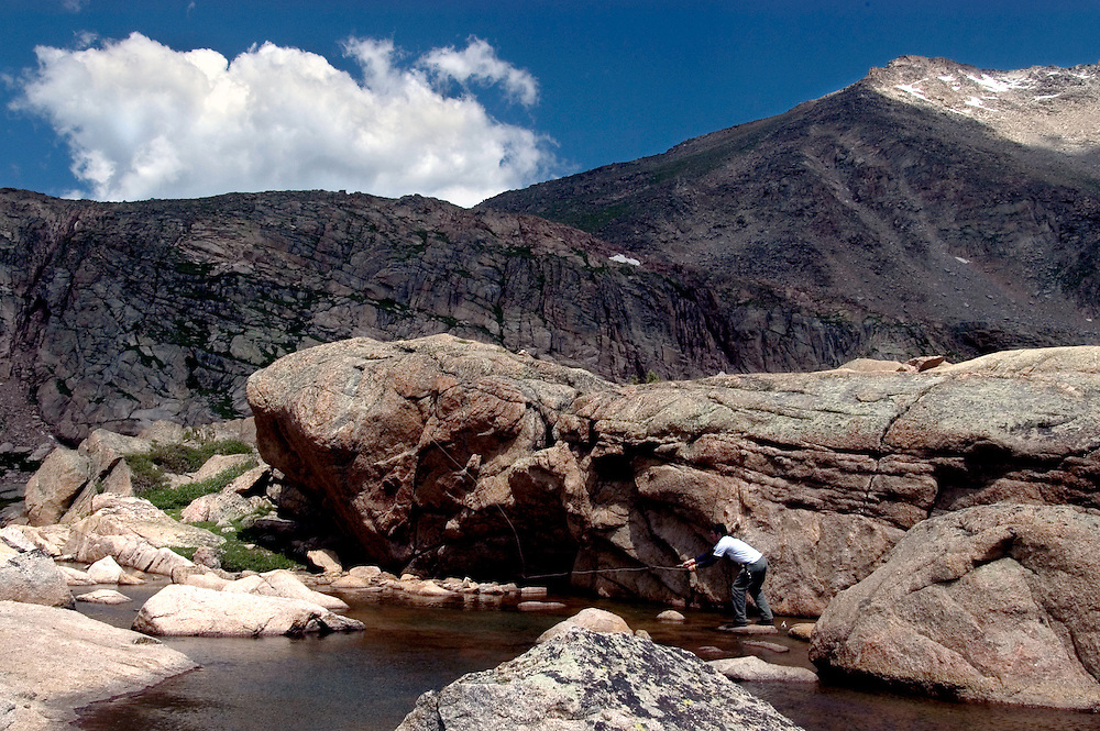 Fly fisherman fishes a high mountain lake in Colorado