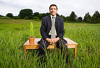 A portrait of a late 30's early 40's mixed ethnicity (spanish french hispanic italian) businessman sitting on a desk in a field of high grass...Model Release: 20080602_MR_A