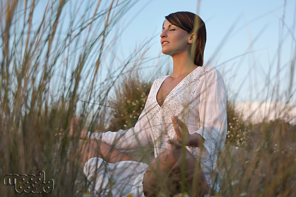 Young woman meditating on sand dunes