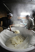 Brewery staff hands shovel out steaming rice onto a conveyor belt where it is cooled at the beginning of the brewing process of sake, a wine-like beverage fermented from rice, water, yeast and a starch-killing mold called koji-kin, at a sake brewery in Kyoto, Japan. More than 1,200 sake breweries exist in Japan, though falling domestic consumption has lead some to look to  overseas markets...Photographer: Robert Gilhooly