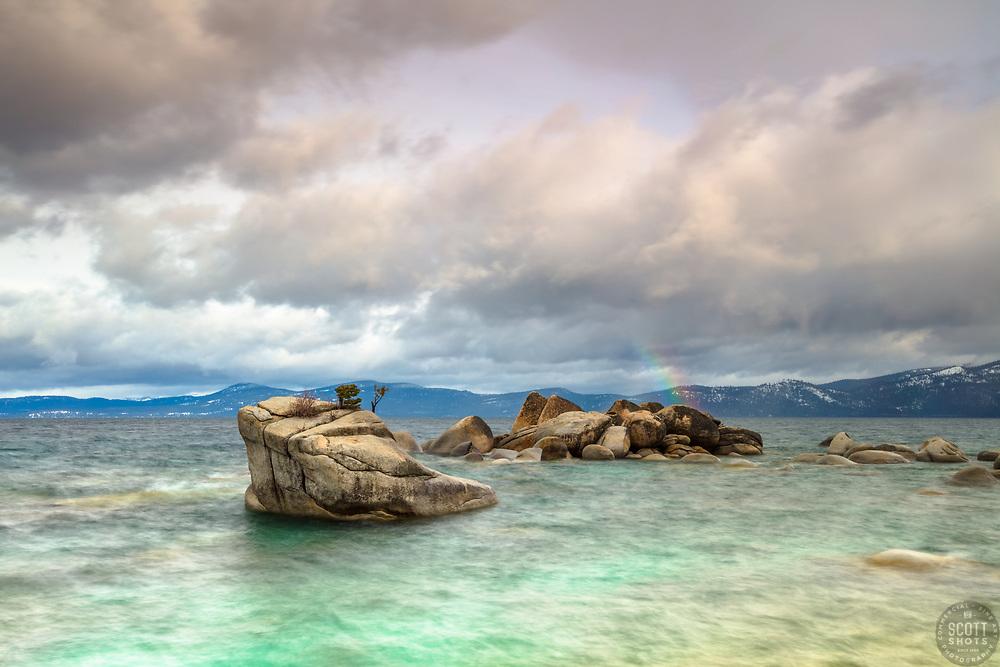 """Rainbow at Bonsai Rock"" - Photograph of a faint rainbow at Bonsai Rock on the east shore of Lake Tahoe, shot at sunrise."