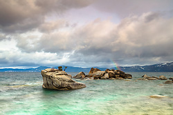 """Rainbow at Bonsai Rock"" - Photograph of a faint rainbow at Bonsai Rock on the east shore of Lake Tahoe, shot at sunrise."