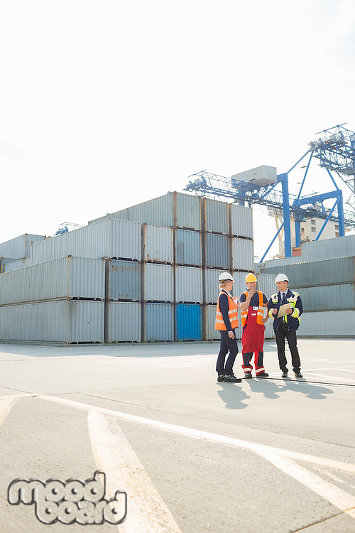 Full-length of workers talking in shipping yard