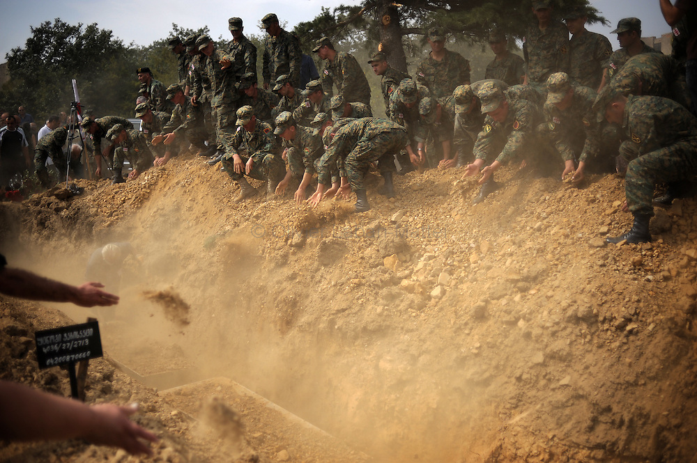 Georgian soldiers cover with dirt the mass grave in which lay down the coffins of unknown georgian soldiers killed in south ossetia, on August 30, 2008, during military funerals in Mukhadgverdi, west of Tbilisi. Russian President Dmitry Medvedev called Saturday on European governments to send more observers to Georgia, a Kremlin statement said.