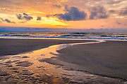 Tidepool emptying into the Atlantic Ocean at sunrise in Corolla on the Outer Banks of NC.