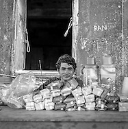 A young Cambodian man sits behind a pile of refreshments and snacks for sale in front of the Bokor Palace Hotel ruins at <br /> <br /> Bokor Hill Station, Preah Monivong National Park, Bokor, Kampot, Cambodia, 2005, Southeast Asia