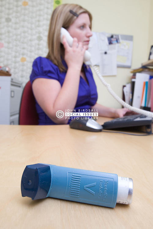 Office worker; who has asthma; sitting at her desk making a phone call with her inhaler close at hand,