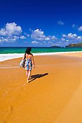 Woman walking along Secret Beach (Kauapea Beach), Island of Kauai, Hawaii
