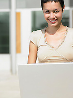 Young woman sitting in plaza courtyard  using laptop portrait