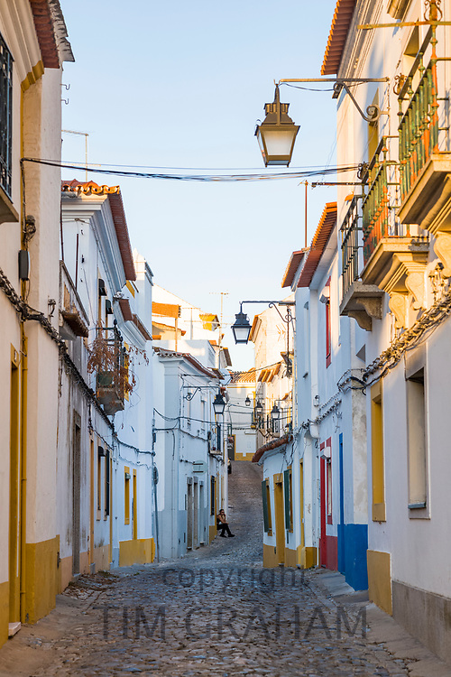 Young person in typical street scene of white and yellow houses, lanterns and narrow cobble street in Evora, Portugal