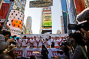 Competitive eater Joey Chestnut works his way through his 18th slice of pizza in the Famous Famiglia world championship pizza eating contest in New York City's Times Square. (Joey Chestnut is included in the book What I Eat: Around the World in 80 Diets.) He won the $5,000 first prize after eating 45 slices of cheese pizza in 10 minutes.  Each slice weighed 109 grams (3.84 ounces) and contained 260 calories. In ten minutes Joey consumed 10.81 pounds (4.9 kilograms) of pizza and drank a gallon of water. The pizza contained 11,700 calories. Joey is on stage between the man in the blue cap and the man with the mohawk hairstyle.