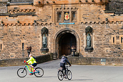 Edinburgh, Scotland, UK. 18 April 2020. Views of empty streets and members of the public outside on another Saturday during the coronavirus lockdown in Edinburgh. People exercising on bicycles at the closed Edinburgh Castle. Iain Masterton/Alamy Live News