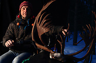 Kjell Magne Eira, reindeer herdsman, sits on his snowmobile with the massive antlers of one of last year's animals.