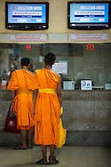Two Buddhist monks queueing to buy train tickets at Hualamphong Railway Station in Bangkok, Thailand