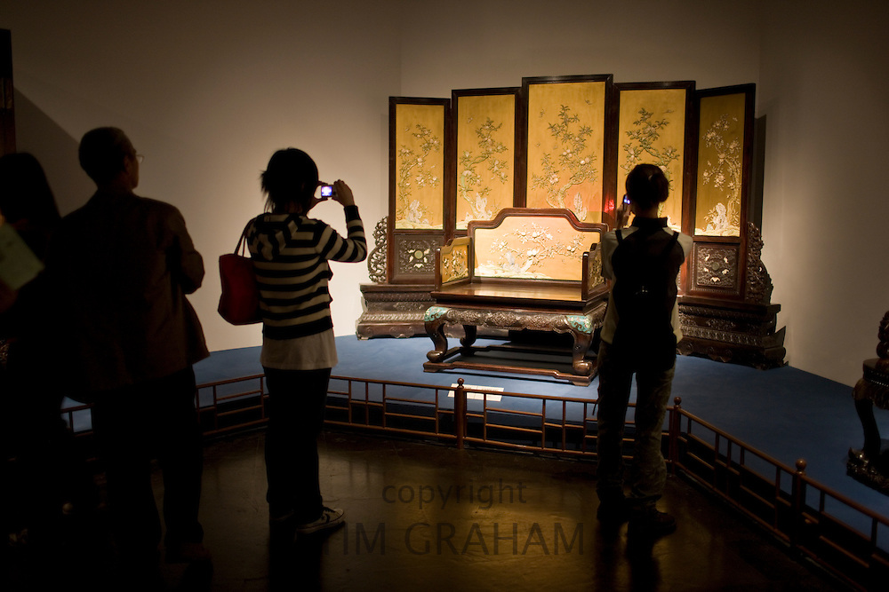 Visitors look at Qing throne on display in glass case at the Shanghai Museum, China