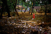 Girl in a red dress playing beneath some palm trees in a field littered with trash. Calangute, Goa, India