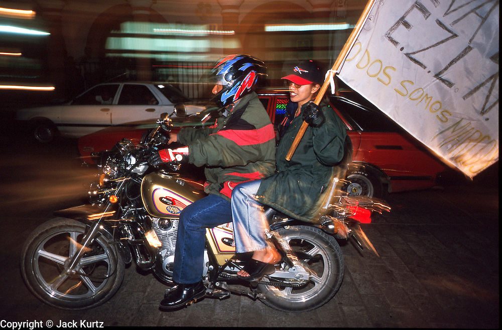 FEB 24, 2001 - SAN CRISTOBAL DE LAS CASAS, CHIAPAS, MEXICO: Supporters of  the EZLN (Zapatistas) ride a motorcycle through San Cristobal de las Casas, Chiapas, Mexico, with a pro-Zapatista banner made from a bedsheet, during a Zapatista march, Feb. 24, 2001. The march was to mark the beginning of the Zapatista's caravan from San Cristobal de las Casas to Mexico City. About 3,000 Zapatistas participated in the march through San Cristobal. The Zapatistas went to Mexico City to press their demands for the passage of the San Andres Accords, signed between the Zapatistas and the Mexican government in 1996 but stalled in the Mexican congress by the formerly ruling Institutional Revolutionary Party. © Jack Kurtz  INDIGENOUS   POVERTY   GLOBALIZATION    POVERTY  WAR   HUMAN RIGHTS    CIVIL RIGHTS