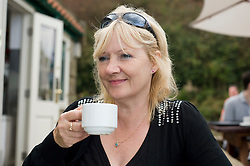Attractive blonde older Woman Drinks tea or coffee outside a small cafe Robin Hoods Bay north Yorkshire.