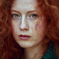 Close-up portrait of female youth with red curly hair and piercing green eyes.