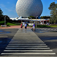 Walking Towards Main Gate of Epcot in Orlando, Florida <br /> These people walking from the parking lot towards the main gate next to Spaceship Earth are a few of the 12 million guests who annually visit Epcot. Its name is an acronym for Experimental Prototype Community of Tomorrow.  When the Walt Disney Company opened it on October 1, it was their second theme park in Bay Lake, a city they have controlled since it was incorporated in 1967.  The municipality has a population of less than 50 people.