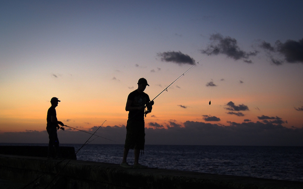 Fishermen stand on the sea wall of the Malecon in Havana as the sun sets. Travel images from Havana Cuba. Pictures by Chris Pavlich Photography.
