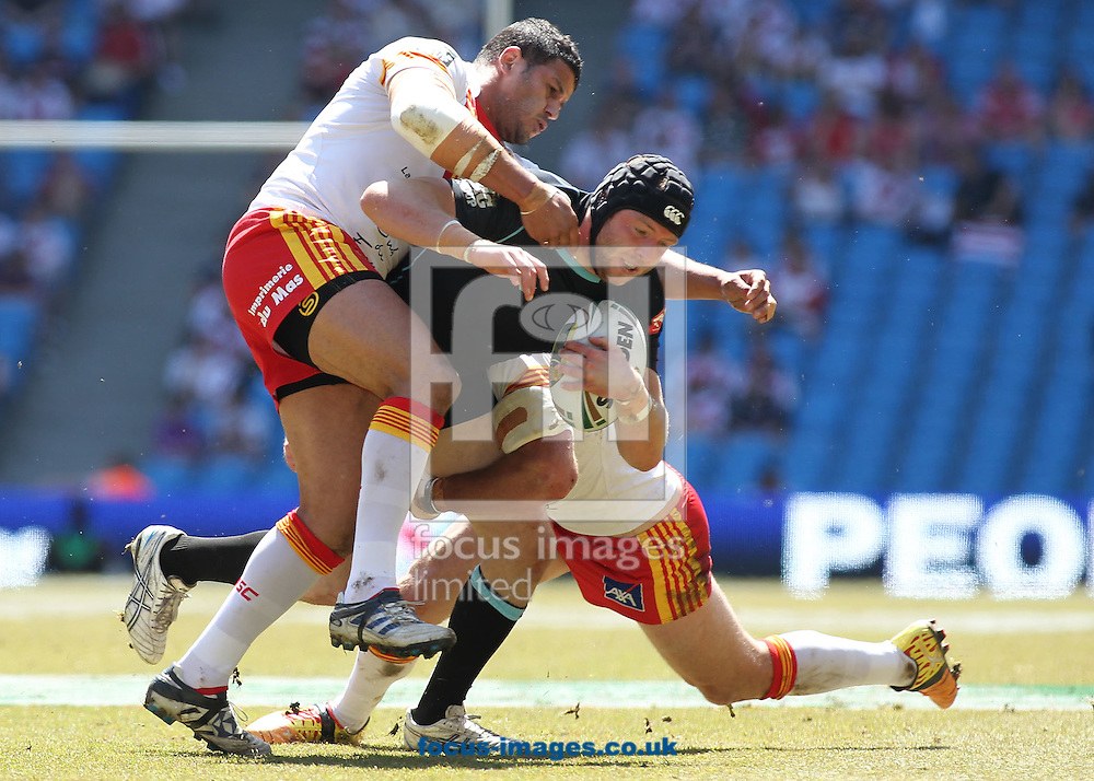 Picture by MIchael Sedgwick/Focus Images Ltd. 07900 363072.27/05/12.Ben Bolger of the London Broncos is tackled by the Catalan Dragons defence during the Stobart Super League 'Magic Weekend' match at the Etihad Stadium, Manchester.