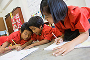 "19 FEBRUARY 2008 -- SANGKLABURI, KANCHANABURI, THAILAND: Burmese refugee children study Thai in a first grade class at Baan Unrak School. Classes at the school are taught in Thai, but many of the refugee children don't speak Thai so they have to take remedial classes. Baan Unrak children's home and school, established in 1991 in Sangklaburi, Thailand, gives destitute children and mothers a home and career training for a better future. Baan Unrak, the ""Home of Joy,"" provides basic needs to well over 100 children, and  abandoned mothers. The home is funded by donations and the proceeds from the weaving and sewing shops at the home. The home is a few kilometers from the Burmese border. All of the women and children at the home are refugees from political violence and extreme poverty in Burma, most are Karen hill tribe people, the others are Mon hill tribe people. The home was started in 1991 when Didi Devamala went to Sangklaburi to start an agricultural project. An abandoned wife asked Devmala to help her take care of her child. Devmala took the child in and soon other Burmese women approached her looking for help.    Photo by Jack Kurtz"