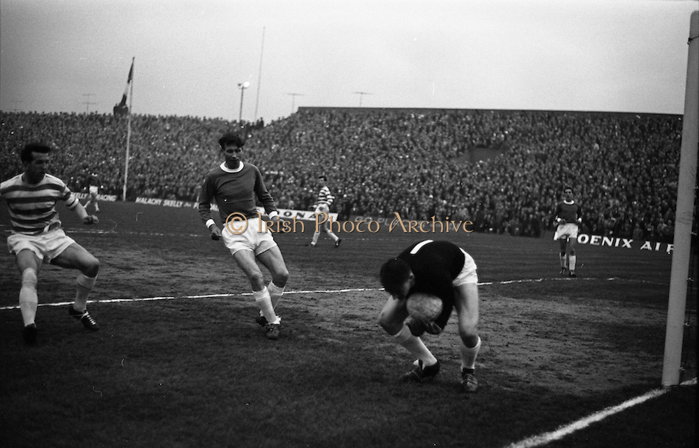 28/04/1965<br /> 04/28/1965<br /> 28 April 1965<br /> F.A.I. Cup Final replay Shamrock Rovers v Limerick at Dalymount Park, Dublin. Rovers won the title 1-0. Mooney (Rovers) is foiled by Limerick Goalie Fitzpatrick as he rushes in to follow up from a corner while Ewan Fenton (Limerick) keeps cover.