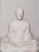 Life like sculpture sitting in lotus position.
