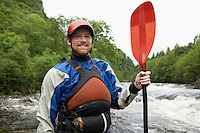 Man holding kayak oar by river portrait