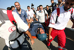16.10.2015, Gaza city, PSE, Gewalt zwischen Palästinensern und Israelis, im Bild Zusammenstösse zwischen Palästinensischen Demonstranten und Israelischen Sicherheitskräfte // Palestinian medics carry an injured journalist during clashes between Palestinian protesters and Israeli security forces at the Erez crossing checkpoint in the northern Gaza Strip October 16, 2015. The unrest that has engulfed Jerusalem and the occupied West Bank, the most serious in years, has claimed the lives of 35 Palestinians and seven Israelis. The tension has been triggered in part by Palestinians' anger over what they see as increased Jewish encroachment on Jerusalem's al-Aqsa mosque compound, Palestine on 2015/10/16. EXPA Pictures © 2015, PhotoCredit: EXPA/ APAimages/ Ashraf Amra<br /> <br /> *****ATTENTION - for AUT, GER, SUI, ITA, POL, CRO, SRB only*****