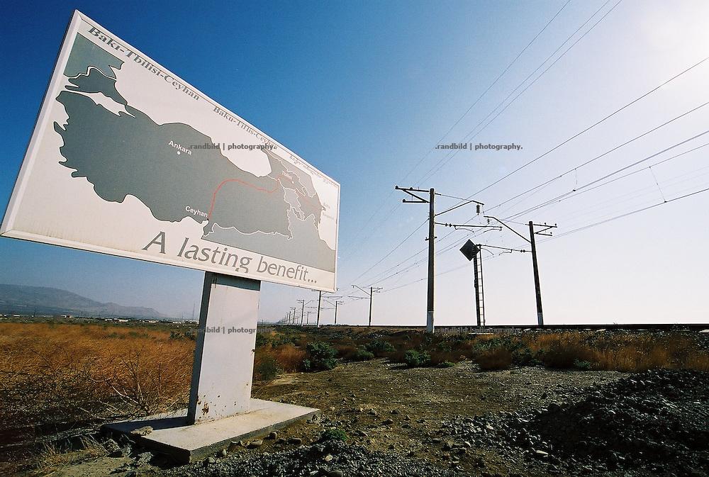 """""""A lasting benefit - eine nachhaltiger Gewinn"""", steht auf dem Werbeschild für die neue Rohölpipeline BTC südlich von Baku. Nebenan die Gleisverbindung nach Georgien, über die noch Tankwagen das Öl zu einem Terminal transportieren...A lasting Benefit - Billboard for BTC Pipeline near Baku."""
