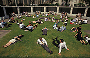 City office workers stretch out over the lush grass during a hot summer lunchtime in Trinity Square in the City of London, on 18th July 1993, in London, England. Dozens of other co-workers  also enjoy the inner-city heatwave in the early nineties. .