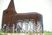Apr 04, 2016 - Borgloon, Belgium - Shows a ''see-through church'', a site specific work entitled ''Reading between the lines'' outside Belgian town of Borgloon. Completed in 2011 by the Belgian architects duo Gijs Van Vaerenbergh, the project is 10 meters high and is made of 100 layers and 2000 columns of steel. Depending on the perspective of the viewer, the church is either perceived as a massive building or seems to dissolve -- partly or entirely -- in the landscape. On the other hand, looking at the landscape from within the church, the surrounding countryside is redefined by abstract lines. The project is frequented by visitors at home and abroad, especially during spring when fruit flowers blossom.  <br />