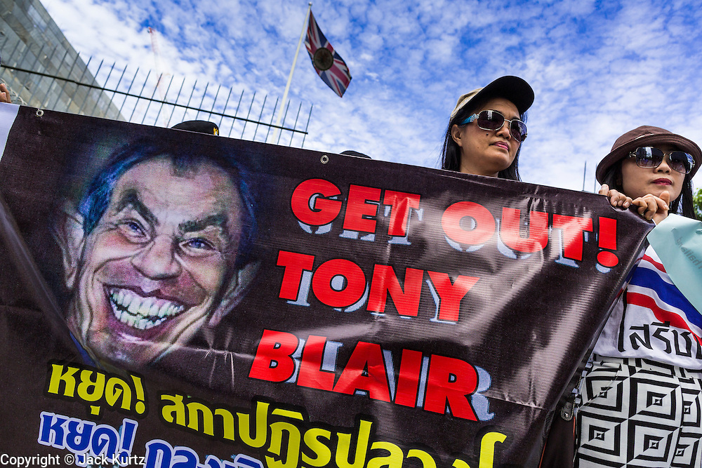 27 AUGUST 2013 - BANGKOK, THAILAND: Thai protesters hold up a poster of Tony Blair in front of the British embassy in Bangkok. About 25 people, including at least two British citizens, picketed the embassy Tuesday morning. They were protesting against former British Prime Minister Tony Blair, who is expected to speak to a political reform commission established by Thai Prime Minister Yingluck Shinawatra. The protest leaders were invited in to the Embassy grounds to speak to representative of the British government. The protest disbanded afterwards. No one was arrested during the protest, which lasted a little over an hour.      PHOTO BY JACK KURTZ
