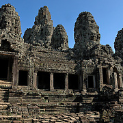 These giant faces carved out of sheer rock loom large against the backdrop of the forest.  <br /> <br /> Angkor Thom (Khmer: អង្គរធំ; literally: &quot;Great City&quot;), located in present day Cambodia, was the last and most enduring capital city of the Khmer empire. It was established in the late twelfth century by King Jayavarman VII. It covers an area of 9 km&sup2;, within which are located several monuments from earlier eras as well as those established by Jayavarman and his successors. At the centre of the city is Jayavarman's state temple, the Bayon, with the other major sites clustered around the Victory Square immediately to the north.<br /> <br /> Angkor Thom was established as the capital of Jayavarman VII's empire, and was the centre of his massive building programme. One inscription found in the city refers to Jayavarman as the groom and the city as his bride.<br /> <br /> Angkor Thom seems not to be the first Khmer capital on the site, however. Yasodharapura, dating from three centuries earlier, was centred slightly further northwest, and Angkor Thom overlapped parts of it. The most notable earlier temples within the city are the former state temple of Baphuon, and Phimeanakas, which was incorporated into the Royal Palace. The Khmers did not draw any clear distinctions between Angkor Thom and Yashodharapura: even in the fourteenth century an inscription used the earlier name. The name of Angkor Thom&mdash;great city&mdash;was in use from the 16th century.<br /> <br /> Faces on Prasat Bayon<br /> The last temple known to have been constructed in Angkor Thom was Mangalartha, which was dedicated in 1295. Thereafter the existing structures continued to be modified from time to time, but any new creations were in perishable materials and have not survived. In the following centuries Angkor Thom remained the capital of a kingdom in decline until it was abandoned some time prior to 1609, when an early western visitor wrote of an uninhabited city, &quot;as fantastic as the Atlantis of Plato&quot;. It is believed to have sustained a