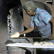 Winter in the Zuni  Pueblo, NM, elderly woman baking bread in traditional oven, this is a special bread only baked for religious celebrations