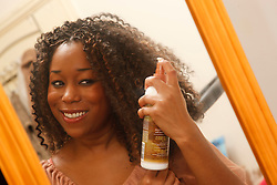 Young black woman putting on hair oil.