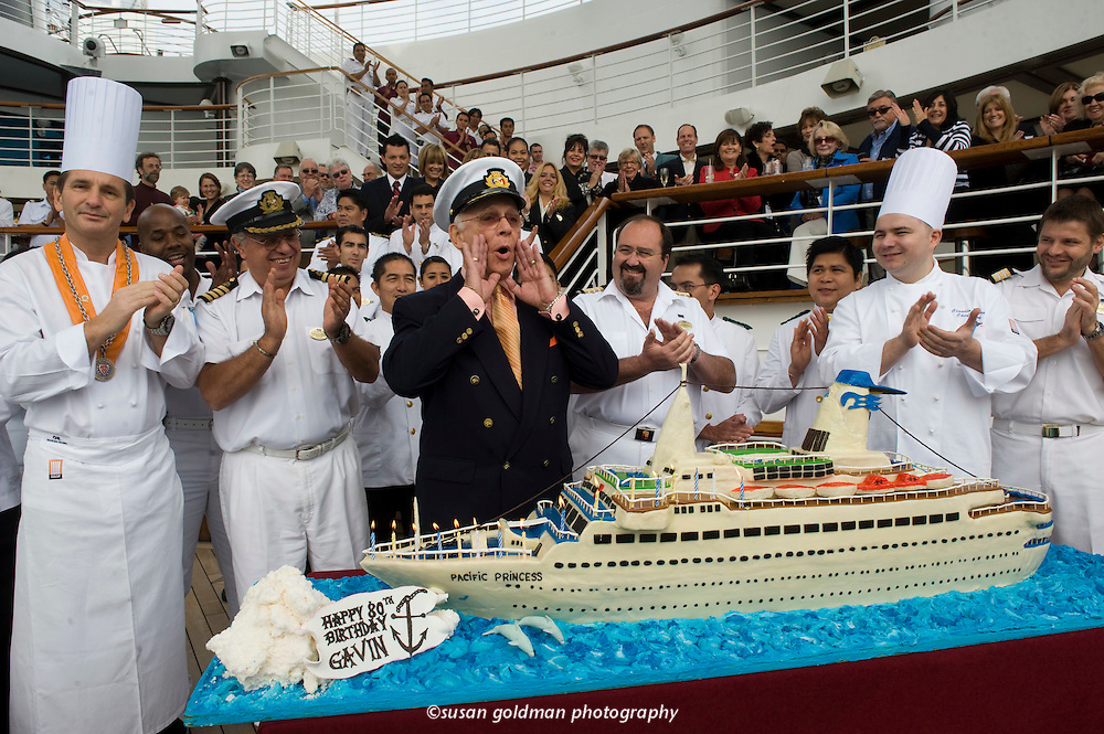 """Gavin MacLeod, Capt. Stubing from television's """"The Love Boat"""", prepares to blow out the candles on his cake as he celebrates his 80th birthday onboard Princess Cruises Golden Princess cruise ship, in the Port of Los Angeles. The cake is a 5 foot long replica of The Pacific Princess, the original Love Boat. Photo/Princess Cruises, Susan Goldman."""