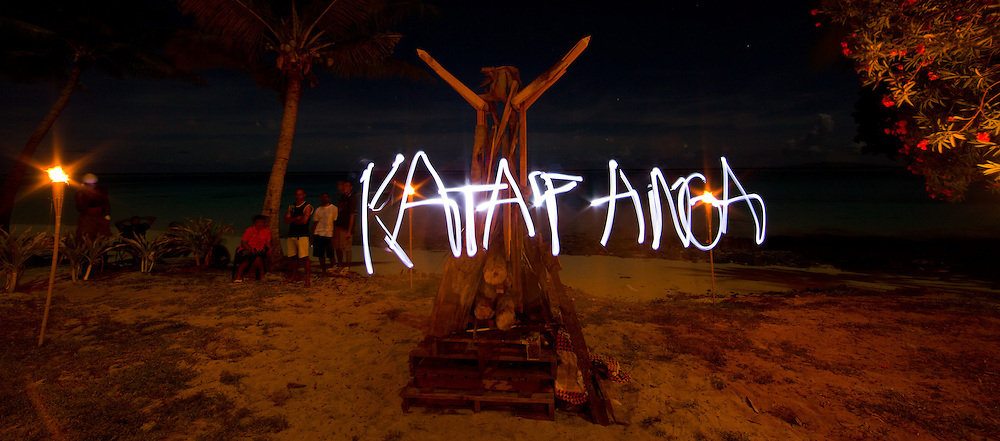 Time Lapse Light Graffiti in front of Wooden Structure on the Beach, Night, Beach Dwellers Watching from Distance, Fiji